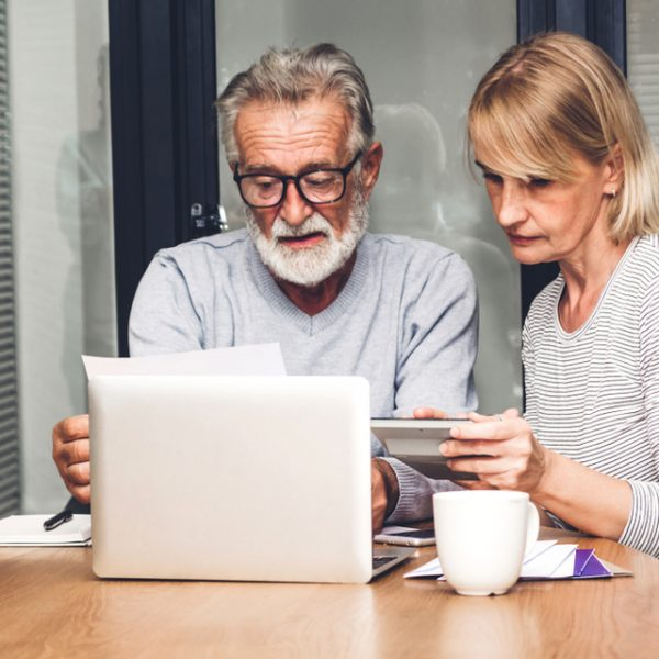 Senior couple sitting at a table and calculating bills